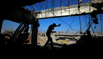 An Iraqi runs through a destroyed building as Iraqi forces battle with Islamic State militants, in the Somod neighbourhood in western Mosul, Iraq March 27, 2017.