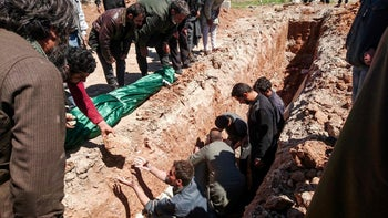 Syrians dig a grave to bury the bodies of victims of a a suspected toxic gas attack in Khan Sheikhun, a nearby rebel-held town in Syria's northwestern Idlib province, on April 5, 2017.