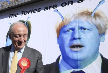Ken Livingstone standing in front of a poster depicting his rival for London mayor, Boris Johnson, as an alien, April 30, 2012.