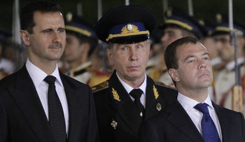 FILE PHOTO: Syrian President Bashar al-Assad (L) and his Russian counterpart Dmitry Medvedev (C) review an honour guard during a welcoming ceremony for the latter at Al-Shaab presidential palace in Damascus on May 10, 2010.
