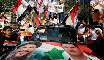 Syrian protesters carry pictures of Hezbollah leader Hassan Nasrallah and Syrian President Bashar Assad in Beirut, Lebanon, July 24, 2011