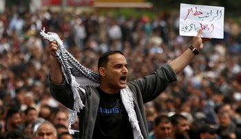 """A PA employee holds a sign that reads """"Salary is a red line. Hamdallah (Palestinian PM), leave"""" during a protest against deductions on their salaries, in Gaza City April 8, 2017."""