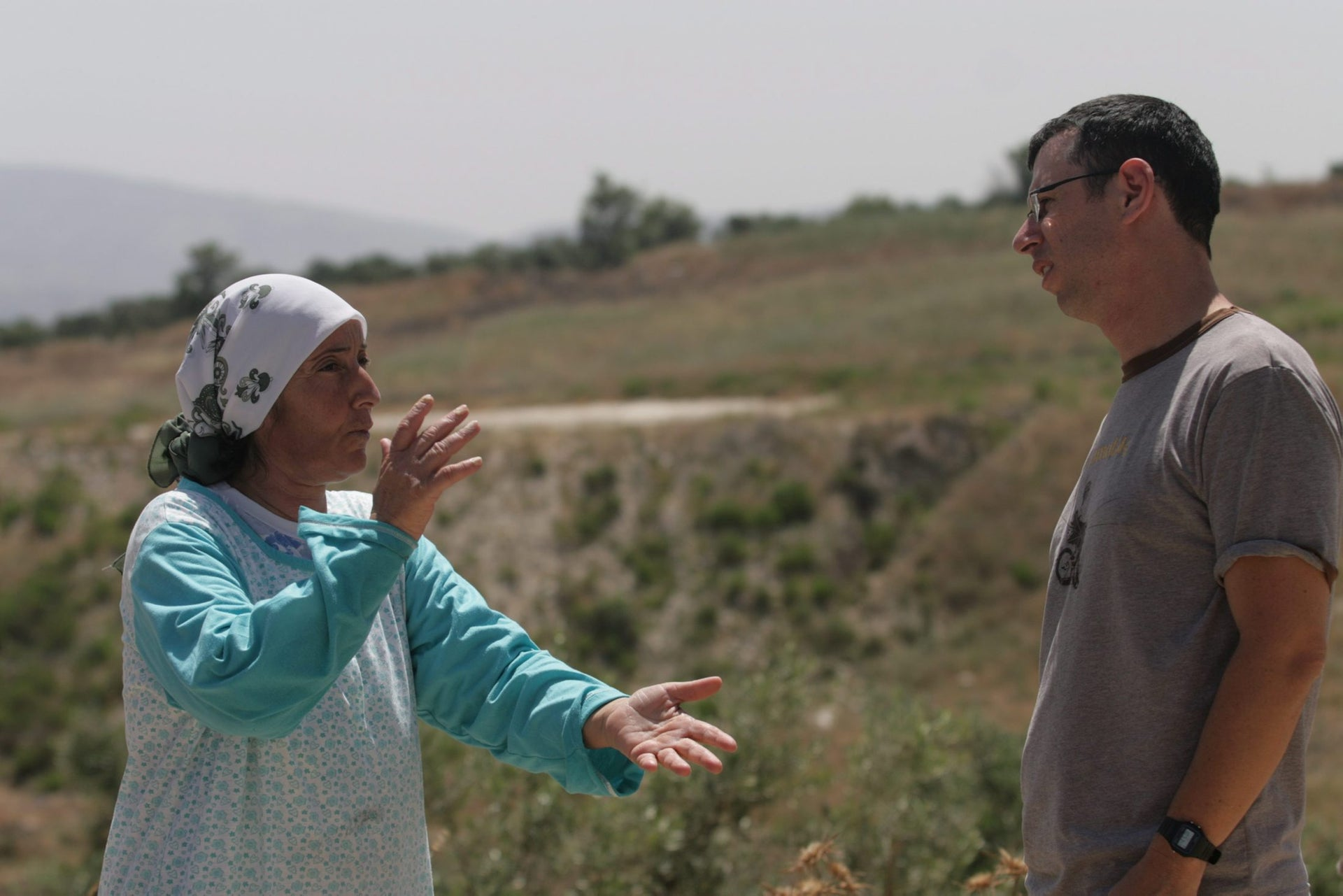 Assaf Gavron speaks with a Palestinian woman near the West Bank settlement of Yitzhar in 2009.