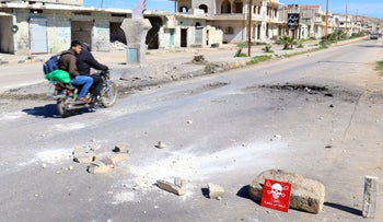 Men ride past a hazard sign at a site hit by an airstrike in the town of Khan Sheikhoun, Syria April 5, 2017.