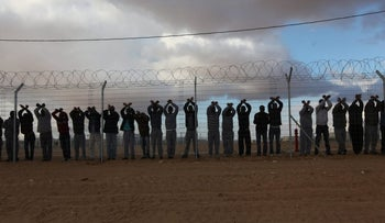 2014 | Southern Israel. Asylum seekers signal their solidarity with hundreds of their fellow migrants through the fence of the Holot detention facility.