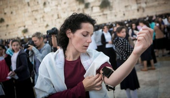 2013 | Western Wall, Jerusalem. A member of Women of the Wall dons tefillin, a religious custom traditionally performed only by men. The group wants to secure the right of women to pray at the site.