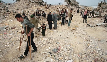 2002 | Jenin, Palestinians walk by the rubble of a building destroyed in an Israel Defense Forces attack when the second intifada was at its peak.