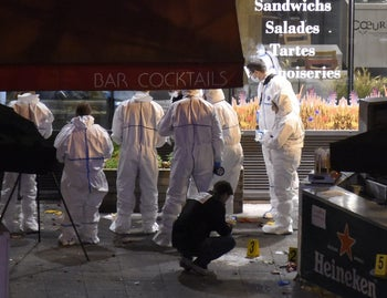 Forensic experts inspect the site of an attack, a restaurant outside the Stade de France stadium in Saint-Denis, north of Paris, November 13, 2015.