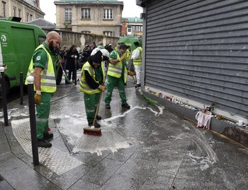 Workers clean the pavement outside the Cambodian restaurant in Paris' 10th district, where 18 people were killed Friday night, November 14, 2015.