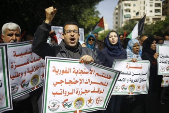 Palestinians shout slogans and hold placards during a protest in Gaza City on April 10, 2017 against a decision by the West Bank-based Palestinian Authority to impose pay cuts on its civil servants in the Gaza Strip.