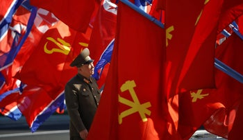 FILE PHOTO: A North Korean soldier checks flags before the opening ceremony for the newly constructed residential complex in Ryomyong street in Pyongyang, North Korea April 13, 2017.