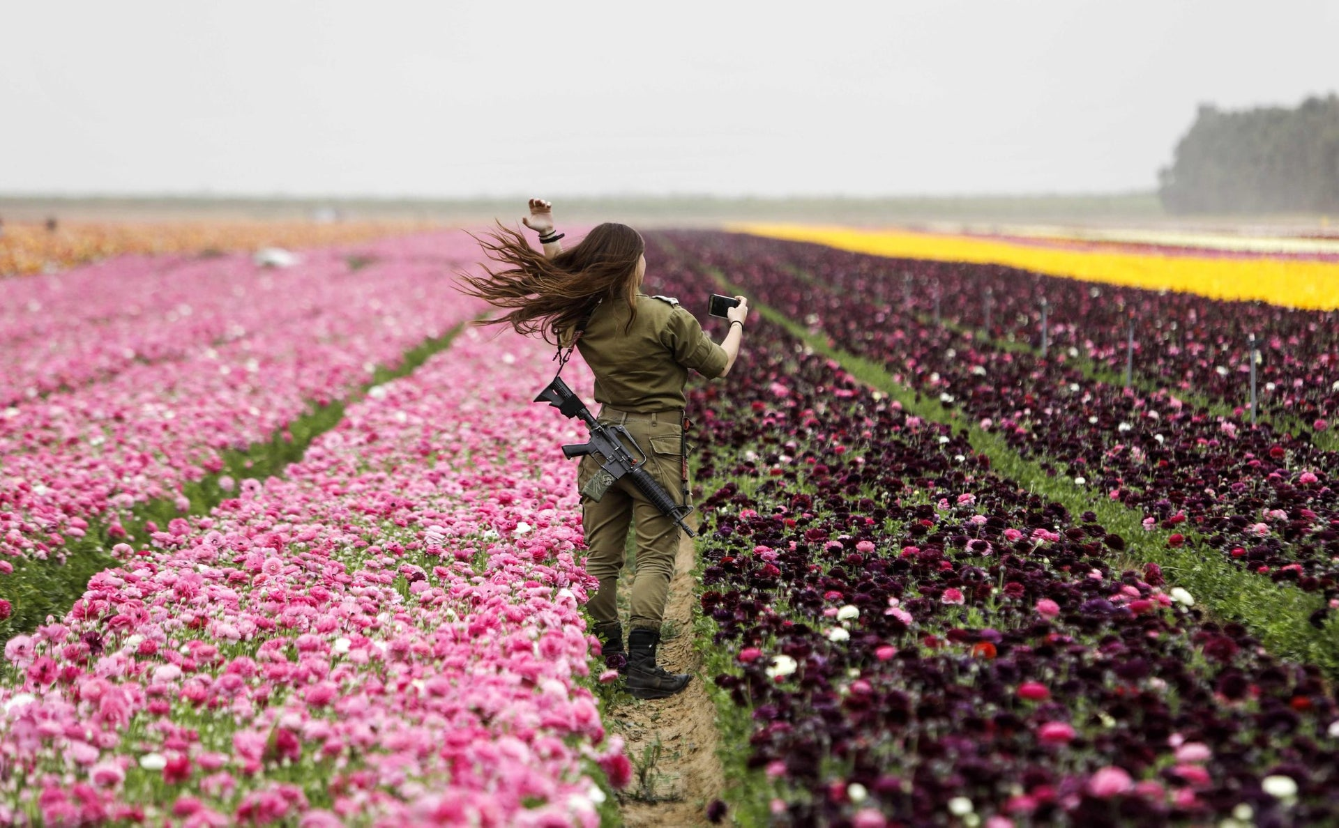 An Israeli soldier looks through her cell phone as she enjoys the Ranunculus flowers in a field in the southern Israeli Kibbutz of Nir Yitzhak, located along the Israeli-Gaza Strip border, during the Jewish holiday of Pesach (Passover) on April 12, 2017.