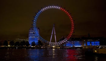 The London Eye ferris wheel is lit up in the colors of the French flag in solidarity with France after the deadly attacks in Paris, in London, Saturday, Nov. 14, 2015.