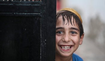 A student covering his head with a Kippah poses for the camera as he leaves the main Talmudic school at Hara Kbira, the main Jewish neighborhood on the Island of Djerba, southern Tunisia,Oct. 29, 2015.