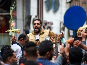 An Egyptian raises a cross made of palm leaves as he is being lifted outside the Coptic Orthodox Patriarchate in Alexandria after a bomb blast struck worshippers on April 9, 2017.