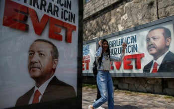 """A Turk walking past """"Yes"""" billboards with images of Turkey's president, Recep Tayyip Erdogan, in Istanbul, Friday, April 14, 2017."""