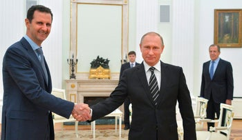 In this Tuesday, Oct. 20, 2015 file photo, Russian President Vladimir Putin, center, shakes hand with Syrian President Bashar Assad as Russian Foreign Minister Sergey Lavrov, right, looks on in the Kremlin in Moscow, Russia