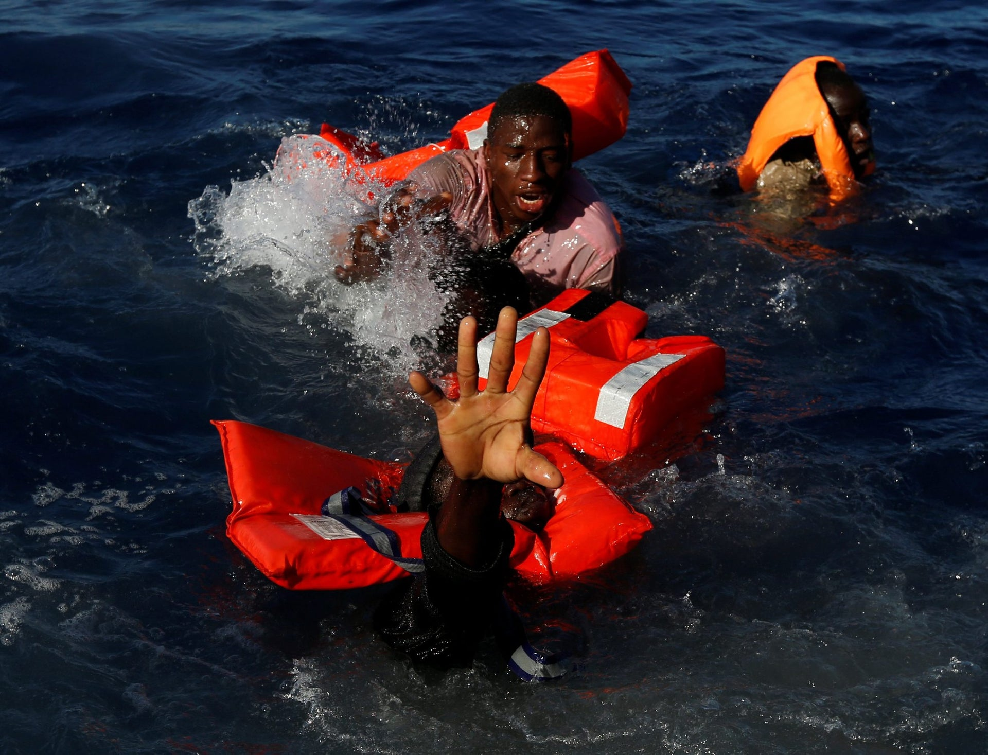 Migrants try to stay afloat after falling off their rubber dinghy during a rescue operation by the Malta-based NGO Migrant Offshore Aid Station (MOAS) ship in the central Mediterranean in international waters