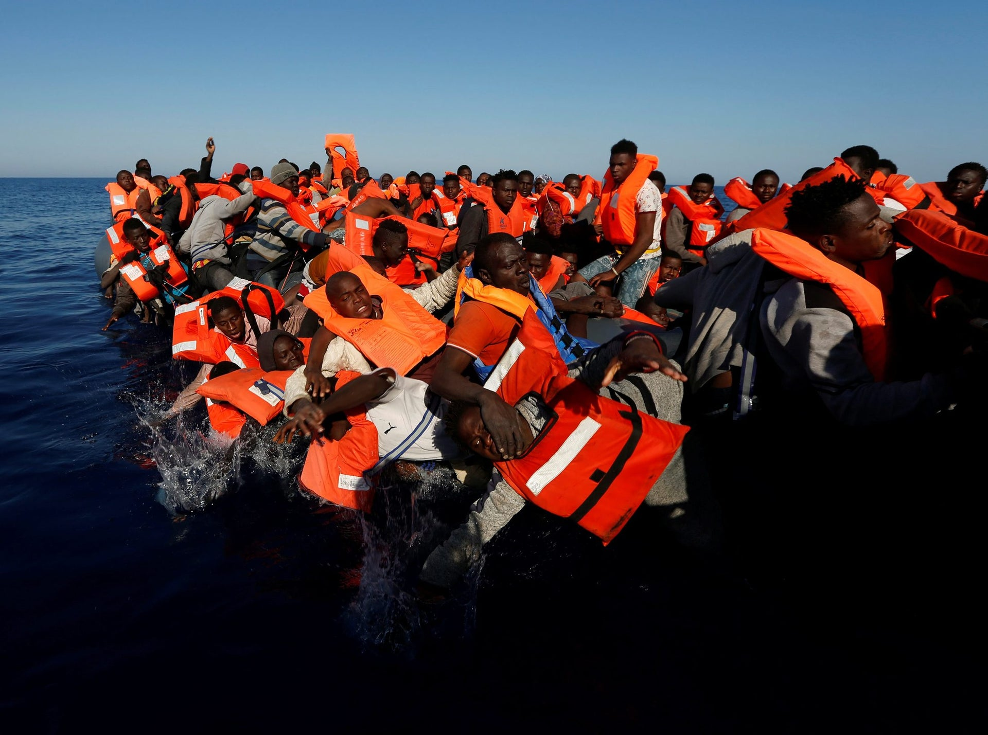 Migrants fall off their rubber dinghy during a rescue operation by the Malta-based NGO Migrant Offshore Aid Station (MOAS) ship in the central Mediterranean in international waters some 15 nautical miles off the coast of Zawiya in Libya, April 14