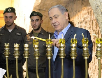 PM Benjamin Netanyahu lighting a menorah at the Western Wall (December 2014): Where did the custom of marking Hanukkah, a holiday initiated by Judah the Maccabee, with fire come from? Not Judah.