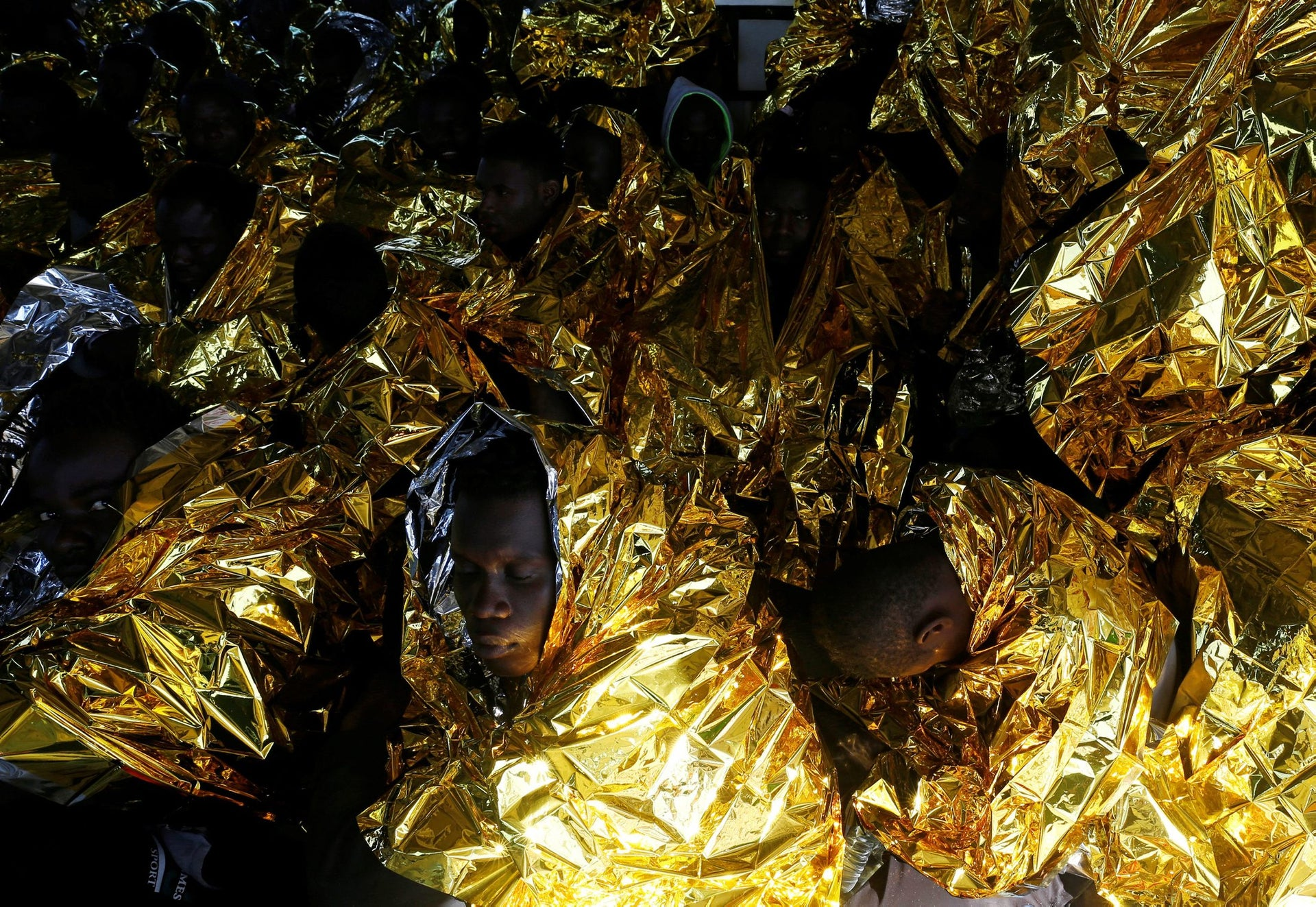 Migrants rest on the deck of the Malta-based NGO Migrant Offshore Aid Station (MOAS) ship Phoenix after being rescued from a rubber dinghy in the central Mediterranean in international waters some 15 nautical miles off the coast of Zawiya in Libya, April 14, 2017.