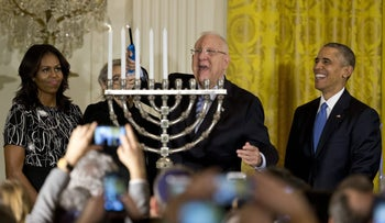 President Reuven Rivlin, second from right, lights the menorah and sings joined by President Barack Obama, right, first lady Michelle Obama, left, and Nechama Rivlin, second from left, during the first of two Hanukkah receptions the East Room of the White House in Washington, Wednesday, Dec. 9, 2015.