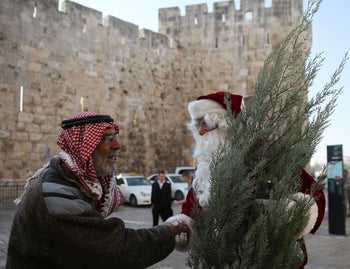 A Palestinian Christian man dressed up as Santa Claus greets a Palestinian Muslim man in Jerusalem's Old City on December 21, 2015.