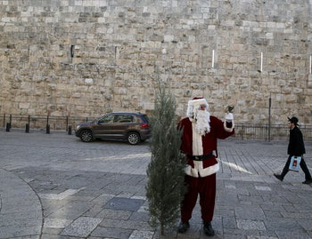 Israeli-Arab Issa Kassissieh wears a Santa Claus costume as he holds a bell and a Christmas tree during the annual distribution of Christmas trees by the Jerusalem municipality just outside Jerusalem's Old City December 21, 2015.