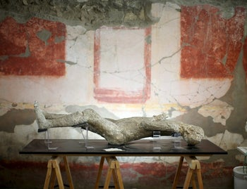 A plaster cast of a Pompeii victim lies in a room decorated with red frescoes in the ancient Roman city. October 13, 2015.