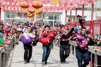 Men run carrying their wives in a contest during the celebration of Nowruz festival in Aksu, China March 21, 2017.