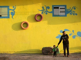 A Palestinian man and a boy stand in front of a house painted by Palestinian artists in the Shati Refugee Camp, December 19, 2015.