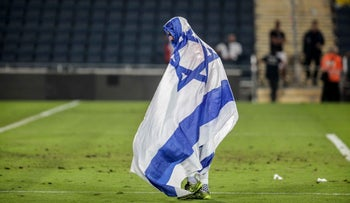 A player draped in the Israeli flag walks on the field at a soccer match between Hapoel Be'er Sheva and Beitar Jerusalem, October 19, 2015.