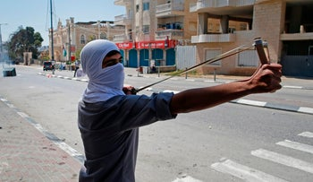 A Palestinian protester uses a sling shot to hurl towards Israeli security forces during clashes following a demonstration in the West Bank town of Bethlehem to show their support for Palestinians imprisoned in Israeli jails after hundreds of detainees launched a hunger strike on April 17, 2017