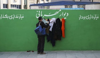 """Iranian man checks clothes hung on hooks at an outdoor charity wall marked, """"Wall of Kindness"""" January 7, 2016."""