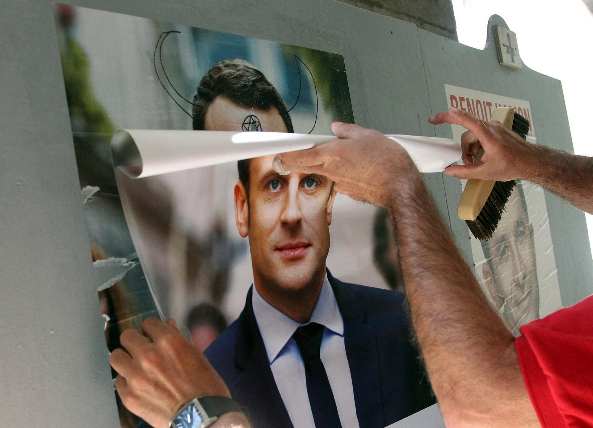 A supporter of French centrist presidential candidate Emmanuel Macron, sticks a campaign poster in Bayonne, southwestern France, April 19, 2017.