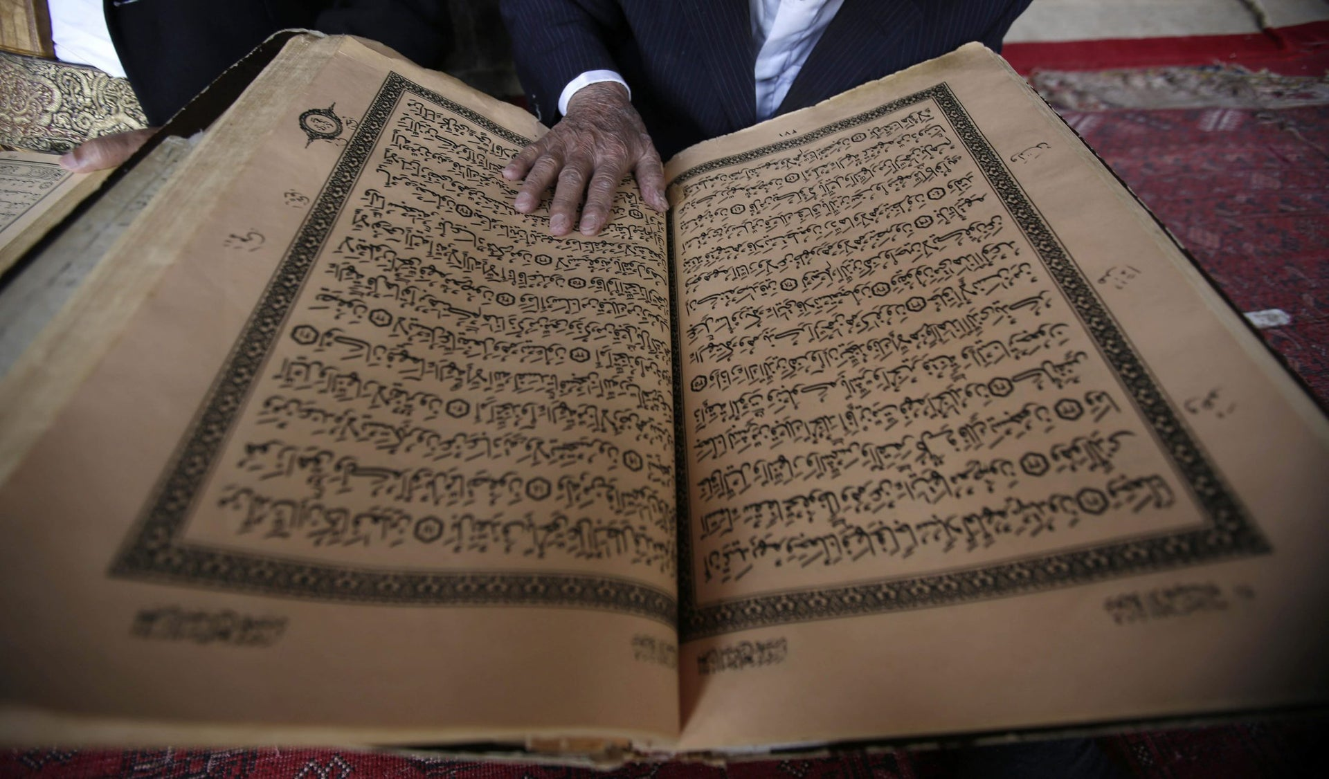 An elderly man reads verses of the Quran, Islam's holy book, on the first day of the fasting month of Ramadan in the Grand Mosque in the old city of Sanaa, Yemen, Monday, June 6, 2016.