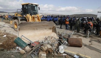 A tractor removes debris blocking a road at the Amona outpost, northeast of Ramallah, on February 1, 2017 as Israeli security forces evict the hardline occupants of the wildcat settlement outpost in line with a High Court ruling that determined the homes were built on private Palestinian land.