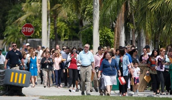 People evacuated because of a bomb threat return to the David Posnack Jewish Community Center and David Posnack Jewish Day School, Monday, Feb. 27, 2017, in Davie, Fla. Jewish centers and schools across the nation are coping with another wave of bomb threats as officials in Philadelphia begin raising money to repair and restore hundreds of vandalized headstones at a Jewish cemetery.