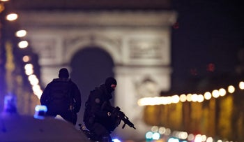 Masked police stand on top of their vehicle on the Champs Elysees Avenue after a policemen was killed and two others were wounded in a shooting incident in Paris, France, April 20, 2017.