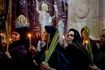 Christians hold candles and palm fonds during the Palm Sunday mass inside the Church of the Holy Sepulchre, April 9, 2017.