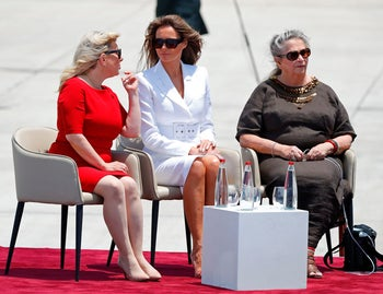 Israeli President's wife Nehama (R), First Lady Melania Trump (C) and Israeli Prime Minister's wife Sara Netanyahu speak upon the US President's arrival at Ben Gurion International Airport in Tel Aviv on May 22, 2017, as part of his first trip overseas. / AFP PHOTO / Jack GUEZ