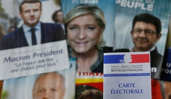 A French voter card in front of pictures of the candidates for the French presidential election, April 22, 2017.