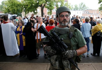 A white supremacist militia member stands in front of clergy counter protesting during rally in Charlottesville, Virginia, U.S., August 12, 2017.