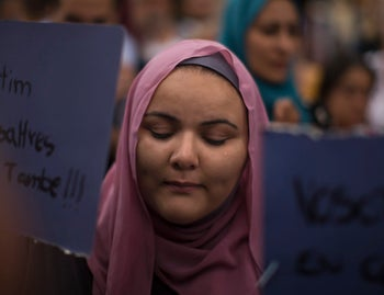 A woman cries as she holds a banner reading in Catalan 'we also suffer it' during a demonstration on Barcelona's historic Las Ramblas promenade, in Spain, Aug. 19, 2017.