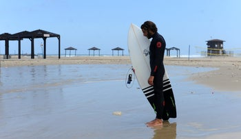Surfer standing at attention on the Mediterranean Sea beachfront as a siren sounds in memory of victims of the Holocaust, in Haifa, April 24, 2017.