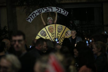 A protester disguised as Sara Netanyahu holds a sign reading 'spin the wheel of misfortune' at a rally against corruption in Netanyahu's government, Tel Aviv, December 23, 2017.