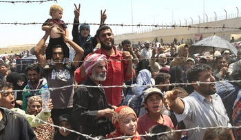 In this June 15, 2015 photo, Syrian refugees gather at the Turkish border as they flee intense fighting in northern Syria.