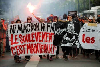 Youths walk behind a banner which reads'Neither Macron, Nor Le Pen - The Uprising is Now' at a protest in Nantes, France, April 27, 2017.