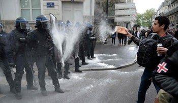 A protester throws flour at French CRS anti-riot police officers during a demonstration against both presidential candidates,  Nantes, western France, on April 27, 2017