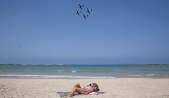 A woman lies on the beach as Israel Air Force planes practice overhead for the Independence Day air show, April 28, 2017.